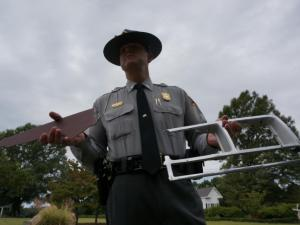 Lt. Jeff Gordan with the North Carolina State Highway Patrol holds pieces of a car found at the scene of a hit-and-run early Sept. 23, 2014, that killed a 13-year-old boy in Wendell.