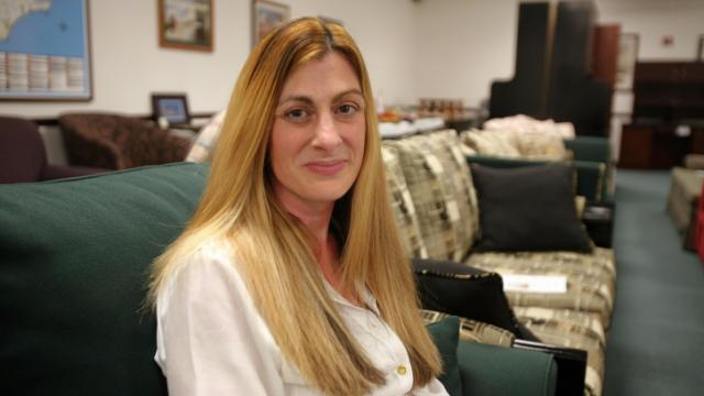 Jennifer Keiffer sits on a piece of inmate-crafted furniture at Correction Enterprises' overstock sale on Sept. 18, 2014. She is one of the few inmates who has risen through the prison ranks to work at the program's headquarters in Raleigh, where she prepares quotes for the quick copy and framing and matting shops, updates the marketing database and works with sales representatives.