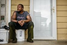 "Mike McFadden sits on his porch in High Point. In the mid-1990s, McFadden said, ""you couldn't even come down this street after about 6 o'clock, when it got dark."""