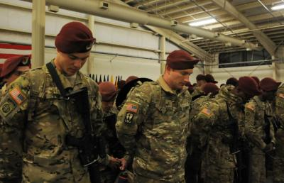 Paratroopers from the 82nd Combat Aviation Brigade bow their heads in prayer prior to being reunited with their Family members and friends after returning from Afghanistan early Friday. Photo by Sgt. 1st Class Joseph Armas/82nd Airborne Division.