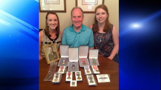 Miranda Dotson (left) with her father, John, sister, Rebecca, and their grandfather's medals. (Photo courtesy of the Dotson family)