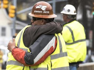 Unidentified workers console one another at a construction site in downtown Raleigh on March 23, 2015, after three people were killed and a fourth person seriously injured in a scaffolding collapse. (Photo courtesy of WWREAVES Photography)