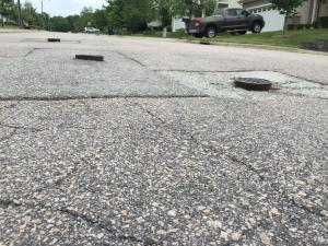 The roads in Ravenstone and nearby Stone Hill Estates were paved by developers, but asphalt was never put down. The incomplete work has left the roads in deteriorating condition, with potholes, crumbling pavement and exposed manhole covers.