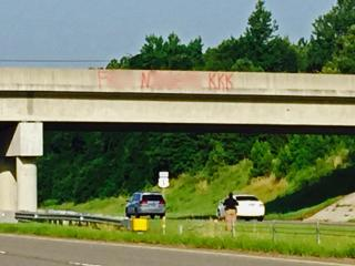 Authorities investigate who painted racist, profane graffiti on a bridge over U.S. Highway 1 near Vass on July 9, 2015. WRAL has blurred parts of the photo. (Photo courtesy of Jamie Jones)