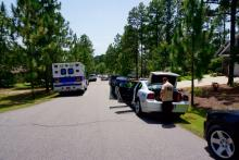 Law enforcement officers on Thursday surrounded the home of the man who was wanted in the death of a 20-year-old woman who was killed after being thrown from a boat trailer Tuesday night.