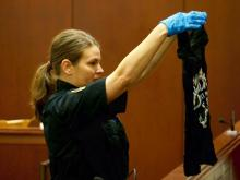 A crime scene investigator shows jurors a bloody T-shirt she said was found in a trash can belonging to Joanna Roberta Madonna.
