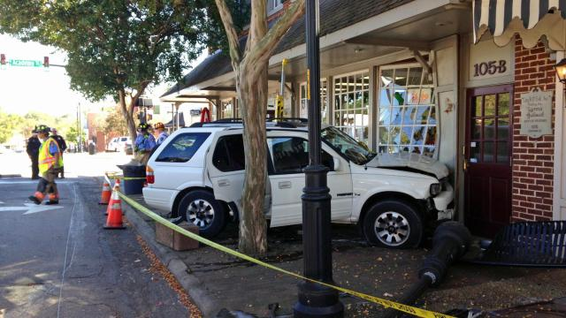 A white SUV slammed into the outside of Ashworth Drugs in Cary Saturday afternoon following a two-vehicle wreck at the intersection of West Chatham and South Academy streets. (Photo by Kara Lysle)