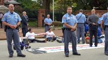 Six people were arrested Thursday, Oct. 30, 2015, after they chained themselves together and sat in front of the Governor's Mansion during a protest of House Bill 318, which bans any North Carolina county or city from restricting local law enforcement's ability to cooperate with federal immigration officials.