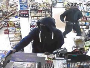 A surveillance image shows two armed men in the process of a robbery at GSK Mini Mart in south Raleigh on Nov. 24, 2015.