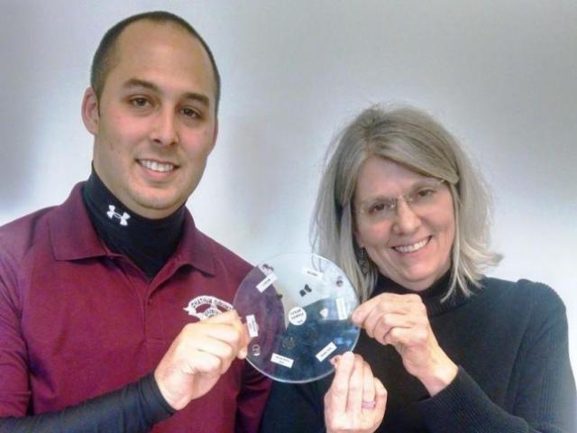 School resource officer Jeremy Timmons and Rose Wignall pose with moon rocks sent to Chatham County by NASA.
