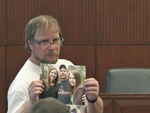 Steven Puryear showed the court a family photo featuring his daughter, Britny, who was killed by a boyfriend in November 2014.