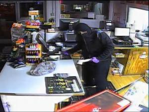 Police are searching for the suspect in an April 1 gas station robbery who was filmed wielding a knife and wearing bright purple rubber gloves.