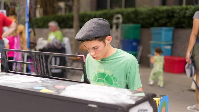 A man plays the piano at one of several pianos set up around Artsplosure. Photos by: Carlton Bassett