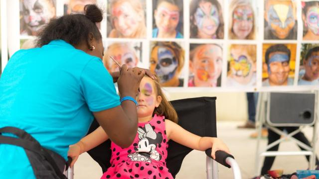 A girl has her face painted with a rainbow butterfly at Artsplosure. Photos by: Carlton Bassett