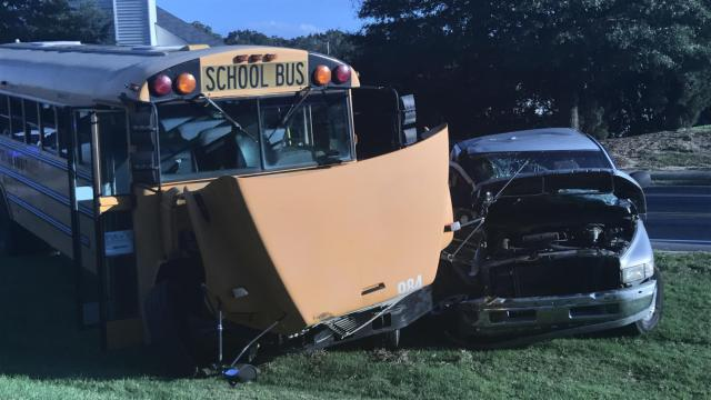 Four people were hospitalized Thursday afternoon following a crash between a pick-up truck and a school bus.