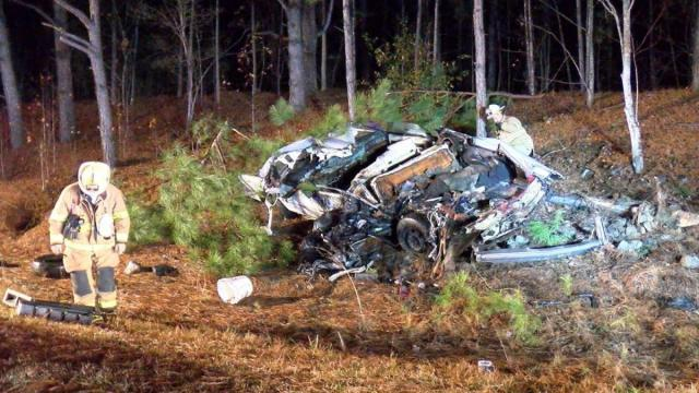 The driver of a Cadillac died and a woman was injured early Tuesday morning when a large truck crashed into the sedan that was stopped on Interstate 40 eastbound in Johnston County.