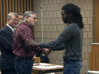 John Franklin McGraw, left, and Rakeem Jones shake hands in a Cumberland County courtroom on Dec. 14, 2016, as McGraw pleaded no contest to charges that he punched Jones during a Donald Trump rally in Fayetteville.