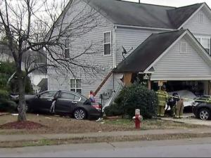 Woman taken to hospital after crashing car into 2 Raleigh homes