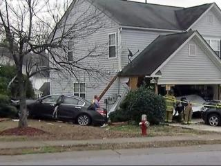 A woman was taken to the hospital for medical attention after she crashed her car into two homes in a Raleigh suburb.