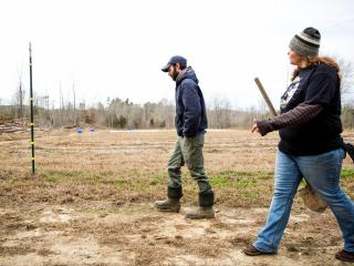 Matt Ballard, farm managers,  and Missy walk out to the crops.  They are working on an aragments of fruits and vegatables as well as cutting trees to build their own shelters.