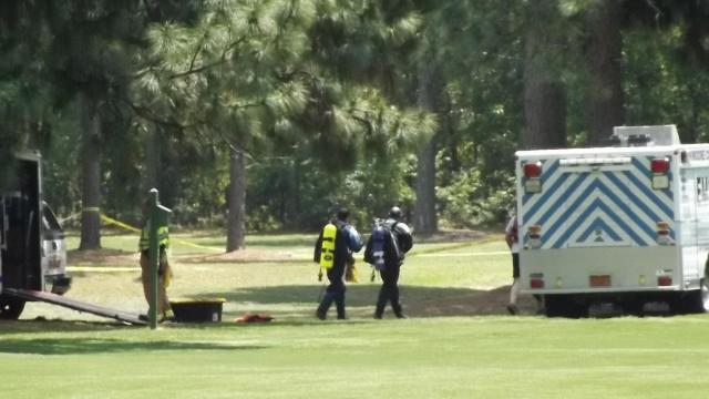 A body was pulled from a pond at a golf course in Southern Pines late Sunday morning after a car became submerged in the water.