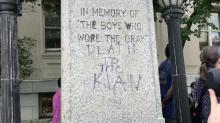 Protesters surround defaced monument
