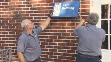 IMAGES: Workers remove name of man tied to racist speech from Durham school