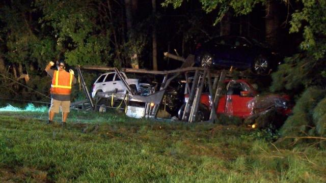 A semi-truck hauling a load of vehicles crashed into the woods near Wilson early Thursday morning after it blew a tire, officials said.