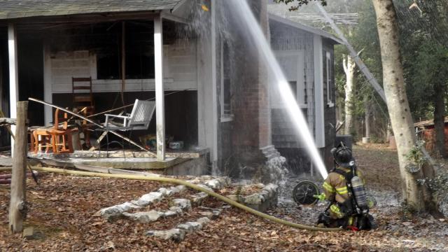 A firefighter battles a Dec. 25, 2017, fire at a home outside Vass. (Photo by Billy Marts/AberdeenTimes.com)