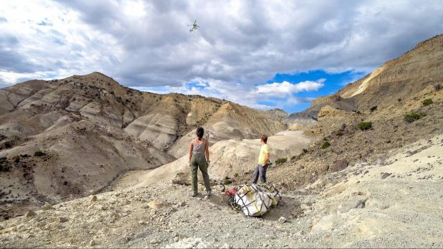Researchers wait for a helicopter to lift plaster-encased dinosaur eggs off a Utah cliff so they could be brought to North Carolina for study. Photo courtesy of N.C. Museum of Natural Sciences)