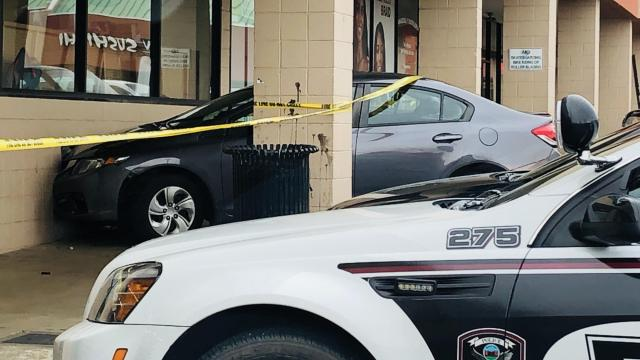 Yellow police tape surrounds a Honda after it slammed into a Dollar General store in Carrboro. (Photo: Carrboro Police)