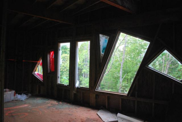 Inside view looking out through six random shaped windows. All are busted out and evening light filters into the second floor of the castle. Taken in Rougemont, North Carolina on September 11, 2019 by Katie Clark.