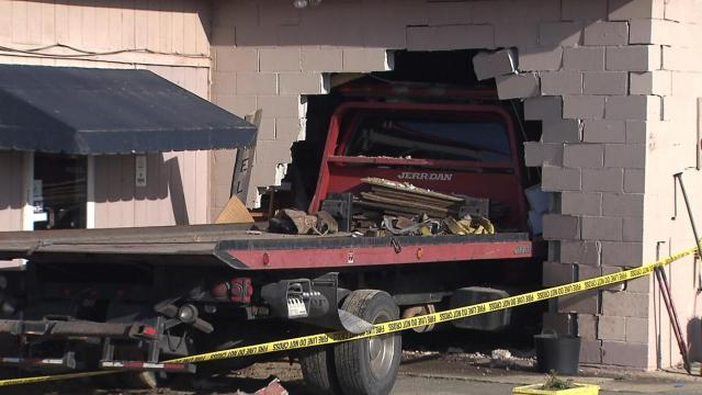 Tow truck crashes into building