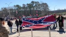 IMAGES: Protesters at a polling site during early voting wave Confederate flags, shout slurs