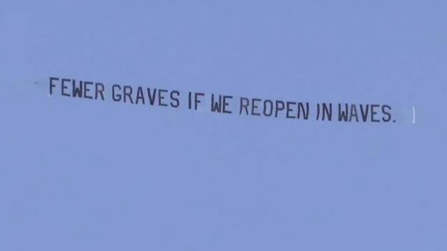 Plane flies over ReOpen NC protest with counter protest message.