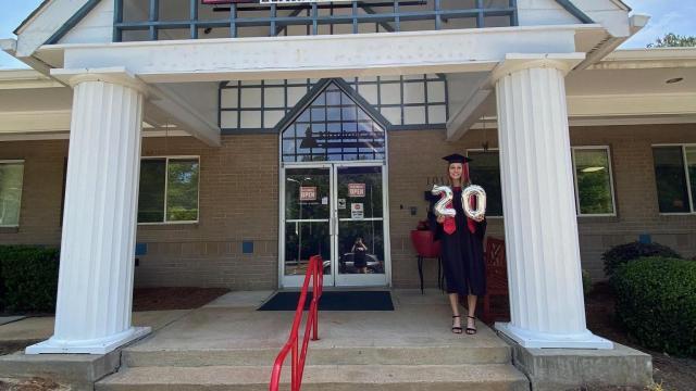 Sarah Barnes celebrates her graduation outside of KinderCare Learning Center
