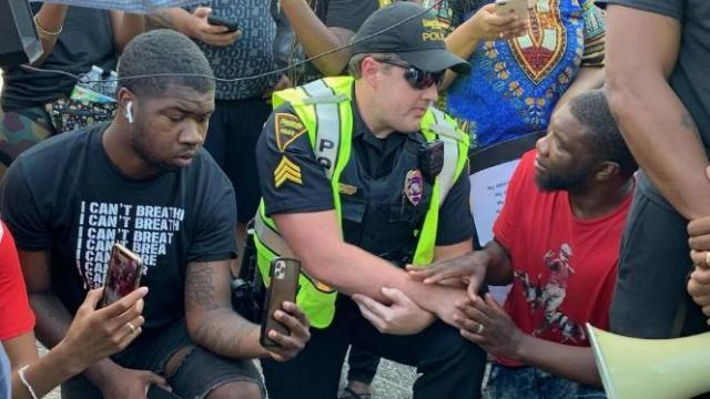 A Fayetteville police officer kneels with protestors.