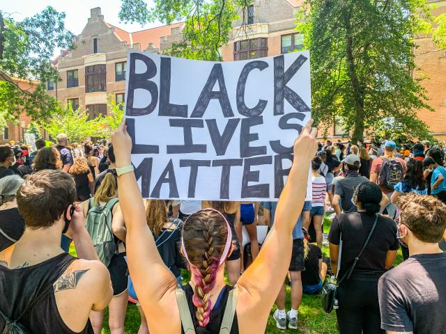 Dozens of young people gathered under the trees on McCorkle Place at the University of North Carolina in Chapel Hill holding signs and listening to speakers.<br/>Photographer: Pete James