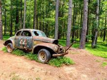 Rusted and abandoned, stock cars can still be found on the speedway, frozen in time.