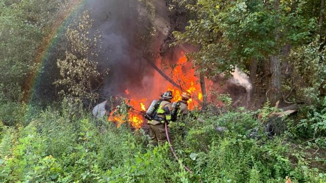 Gaston emergency responders work to put out a fire in the brush off NC Highway 48