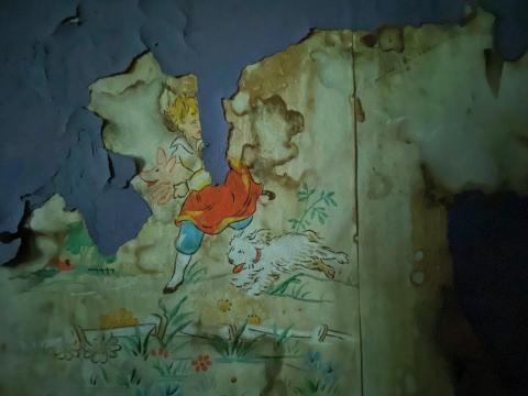 Peeling paint reveals vintage wallpaper beneath.