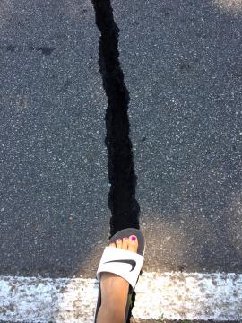 A crack nearly as wide as a human foot could be seen in the asphalt on a road.