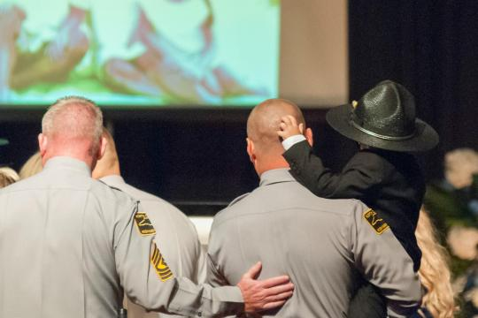 Trooper Pridgen holds the young son of his fallen friend, Trooper Conner, who died in the line of duty. Conner's young son wore Pridgen's hat at his father's funeral.