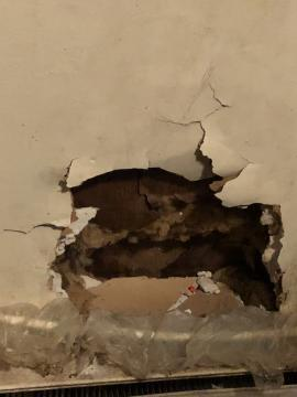 A hole in the wall of Robinson's apartment. The children described roaches crawling out of this hole.