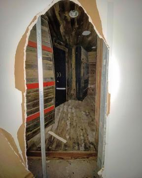A hole was knocked into the drywall, revealing the entrance to the historic tavern.