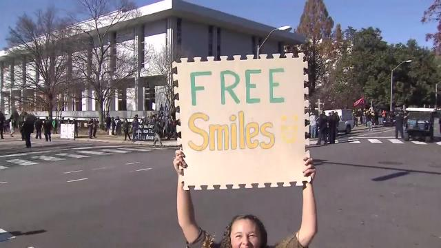 "A young woman held a colorful ""Free smiles"" sign at the protest on Saturday."