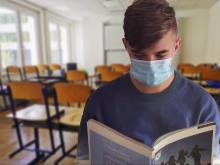 A student reads a textbook wearing a face mask. Photo from Pixabay.