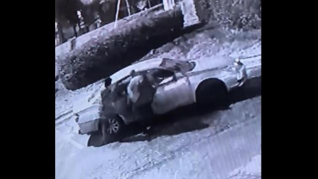 Two suspects were filmed escaping in a silver sedan.