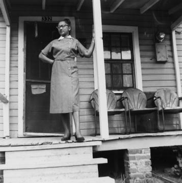 A woman named Jeanette Brown Adams Ferguson poses on the porch of her house on South Street in 1957. She worked at the Sandwich Shop on Wilmington Street for 22 years. Courtesy of the State Archives of North Carolina.