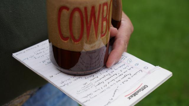 """A man who asked to go by the name """"Cowboy"""" holds notes on prepping and a coffee cup with his nickname on it"""
